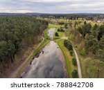 Small photo of Aerial view over small park with a pond in the middle it, Alytus, Lithuania. During cloudy summer day.