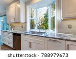 Stock photo luxury home interior boasts amazing kitchen with custom white shaker cabinets topped with granite 788979673