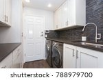 Stock photo laundry room boasts white shaker cabinets brown grey glass tiled backsplash and modern washer and 788979700