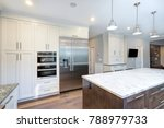 Stock photo luxury home interior boasts amazing kitchen with custom white shaker cabinets endless marble 788979733