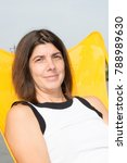 Small photo of forties woman sit on yellow cit in park or sea beach