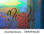 Small photo of Miss you on the mirror of window or Miss you text draw on droplet window of cold misty morning
