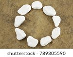 Circle with white pebbles on brown stone chunk