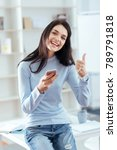 Small photo of Good results. Joyful ambitious pretty woman carrying phone while demonstrating thumb and laughing