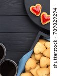 Small photo of Heart shaped cookies decorated for Valentine's Day. Free space for text. Box with heart shaped cookies with coffee, coffee pot, jam on a black wooden table. Two heart shaped cookies with jam.