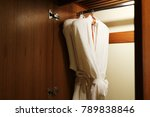 Stock photo two white bathrobes hanging on rack in wooden closet 789838846
