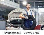 mechanic holding a tire tire at ... | Shutterstock . vector #789916789