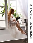 Small photo of Woman using new electronic tablet touch pad with pencil touches the digital screen. Young female sitting near bathroom faucet bath tub at window work place