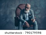 Small photo of Minded, ponder, unhappy rich man in glasses, hold glass with cognac, in tuxedo with red bowtie and pocket square, sit in leather chair over gray background, looking to the side, shares, stock, money