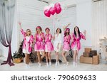 Small photo of Full length portrait of happy lovely girlfriends in pink robes and sleeping masks jumping and having fun at hen party. Bride-to-be in white robe holding pink air balloons with smile standing on tiptoe