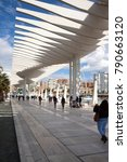 Small photo of Malaga, Spain - March 22, 2016: People walking over the Passeo del Muelle Dos (second dock promenade), a promenade along the harbour of Malaga, opened in 2011.