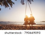 romantic couple in love sitting together on rope swing at sunset beach, silhouettes of young man and woman on holidays or honeymoon