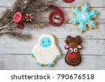 Small photo of Homemade decorated Christmas sugar cookies in shapes of a snowflake, reindeer, and an abominable snowman, isolated on whitewashed wood background with holiday garland
