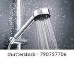 Fresh shower behind wet glass window with water drops splashing. Water running from shower head and faucet in modern bathroom. - stock photo