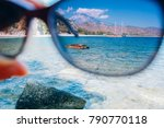 Small photo of hand holding polarization sunglasses against blue sky and sea, summer vacation journey and concept, looking through glasses