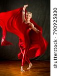 Small photo of Active young woman dancer with short blonde hair, in a red unitard, dramatically swirling red fabric in the studio.
