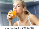 Young Woman Drinking Orange...