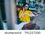 Small photo of Busy businesswoman in eyewear looking at smartwatch while talking on cellular and agree on meeting sitting at laptop computer and working remotely.Manager managing time during phone conversation