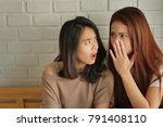 Small photo of disappointed surprised excited woman gossiping, whispering, listening to rumor or hearsay concept, women or girls consulting saying, discussing something in secret