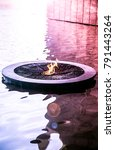 Small photo of Flame burning in a water feature. A water feature with a flame center.