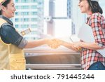 Small photo of Engineer and worker team with helmet handshake together to agree joint business and partnership at construction site.