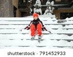 happy boy sitting on snowy... | Shutterstock . vector #791452933