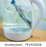 Small photo of A rusty, heated, scaled element in an electric glass teapot. The concept of limescale on the heating elements of household appliances.