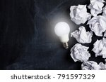 Small photo of Inspiration and imagination concept. lightbulb with white crumpled paper documents