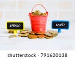 Small photo of Selective focus of red pile with gold coins with blackboard of questions 'SPEND?' or 'SAVE?'. Money saving theme.