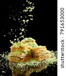 Small photo of Crushed pistachios fall over pieces of baklava