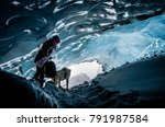 Small photo of Woman exploring athabasca glacier cave in banff / jasper national park canada with adventurous dog pet