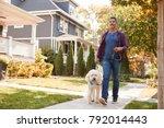 Stock photo man walking dog along suburban street 792014443
