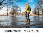 lady standing in flooded street ... | Shutterstock . vector #792575278