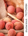 Small photo of High angle view of a tilted basket of fruits (Lichi) of the lychee tree (Litchi chinensis) on coarse sackcloth fabric in an angular basket.