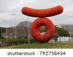 Small photo of Symbolic edifice at the entry of Montpellier University 2, sciences and letters. Form of red sausage and donut on the grass of a traffic circle