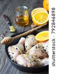 Small photo of Raw food. Chicken legs (drumsticks) with orange and mustard marinade in cast-iron pan on wooden table background. Cooking content