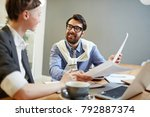 Small photo of Smiling financier with papers having discussion with his associate at meeting