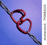 Small photo of Metal silver chain with two red spring hook in the form of hearts as a symbol of strong love.Two red hearts with metal chain isolated on violet paper background. St. Valentines day idea