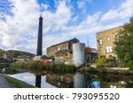 Small photo of Bingley, Airedale, Yorkshire, UK - 012/11/2017 - A riverside factory sits on the bank of the Leeds Liverpool Canal against a blue sky. It is reflected into the water.