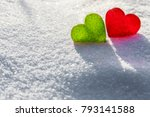 Small photo of Two glass hearts on light background, green and red heart, white snow pattern, love and Saint Valentine day concept