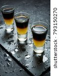 Small photo of Black Shooter - Black Balsam and peach juice. Hard alcoholic shots on stone table.