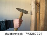 A Man Clogs A Nail With A...