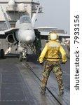 "A ""Yellow Shirt"" Aircraft Director Loads an F/A-18C Hornet onto a Catapult on the Nuclear Aircraft Carrier, USS Enterprise"