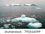 Small photo of Arctic ocean brash ice, with icebergs in the distance on the coast of western Greenland. The salt sea, at freezing point is glazed with icy sheets reflecting the snow-laden sky.