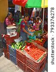 Small photo of CHICHICASTENANGO GUSTEMALA APRIL 29 2016: Portrait of a Mayan people selling fruits and vegetables. The Mayan people still make up a majority of the population in Guatemala