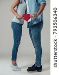 Small photo of Cropped image of beautiful romantic couple isolated on grey background. Young woman is standing on a tiptoe while kissing her handsome man. Holding hands. Happy Saint Valentine's Day!