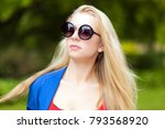 a beautiful blond girl in a park | Shutterstock . vector #793568920