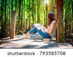 Small photo of woman enjoy reading on wooden bridge under shadow and light of forest tree, feeling relax and comportatble easy listening music online from mobile device in the meanwhile