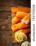 Small photo of Golden oven baked crumbed fish sticks made from hake or whitefish served on paper with lemon and tartare sauce