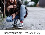Small photo of Close-up of riotous young girl smoking cigarette on the sidewalk